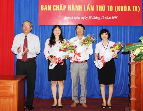 Ông Nguyễn Hòa, Chủ tịch LĐLĐ tỉnh Khánh Hòa, tặng hoa cho 3 cán bộ đảm trách cương vị mới