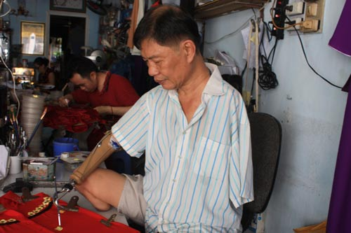 Ông Trần Hùng Bảo miệt mài vẽ hoa trên áo dài thiếu nữ