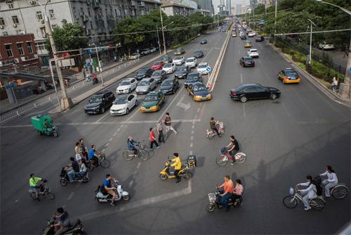 Ôtô riêng, taxi, xe đạp, xe điện và người đi bộ tại một điểm giao cắt ở thủ đô Bắc Kinh hồi tháng 5. Ảnh: New York Times.