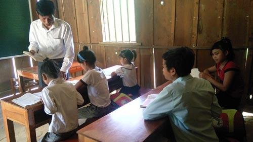 Thầy Hoàng Văn Sáu cần mẫn dạy học cho trẻ bản Đoòng