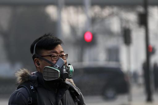 Một người đàn ông đeo khẩu trang chống khói bụi đi bộ ở thủ đô Bắc Kinh hôm 30-12. Ảnh: AP