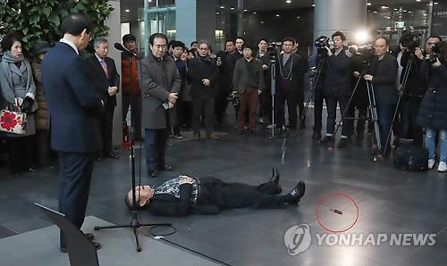 Cụ ông nằm sóng soài trên mặt đất sau khi tự đâm vào bụng trước mặt thị trưởng Park (đứng bên trái). Ảnh: YONHAP