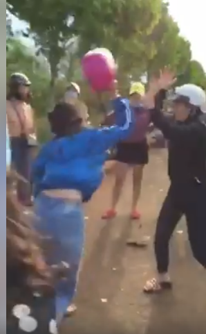 Nữ sinh mặc áo khoác xanh phang mũ bảo hiểm về phía đối phương. Ảnh cắt từ clip