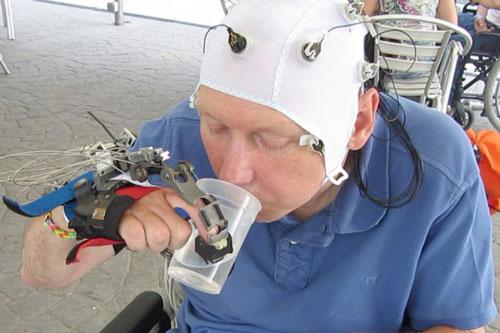 Bàn tay robot sinh học được não điều khiển để cầm cốc nước Ảnh: NEW SCIENTIST