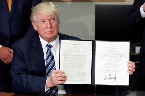 Tổng thống Mỹ Donald Trump ký ban hành một sắc lệnh hành pháp hôm 21-4 Ảnh: REUTERS