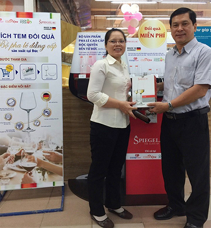 Ông Nguyễn Hữu Đại - Giám đốc Co.opmart Nguyễn Kiệm trao tặng bộ ly vang đỏ cao cấp cho khách