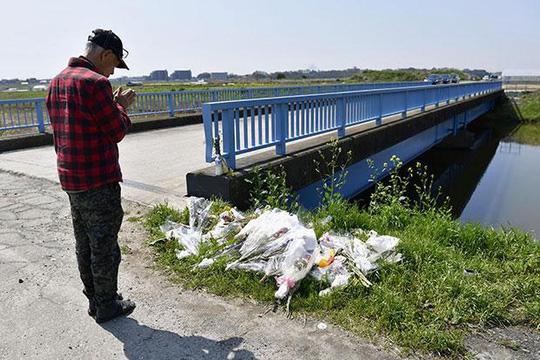 Một người đàn ông cầu nguyện ngày 14-4 tại nơi thi thể bé Lê Thị Nhật Linh được tìm thấy trước đó - Ảnh: KYODO NEWS