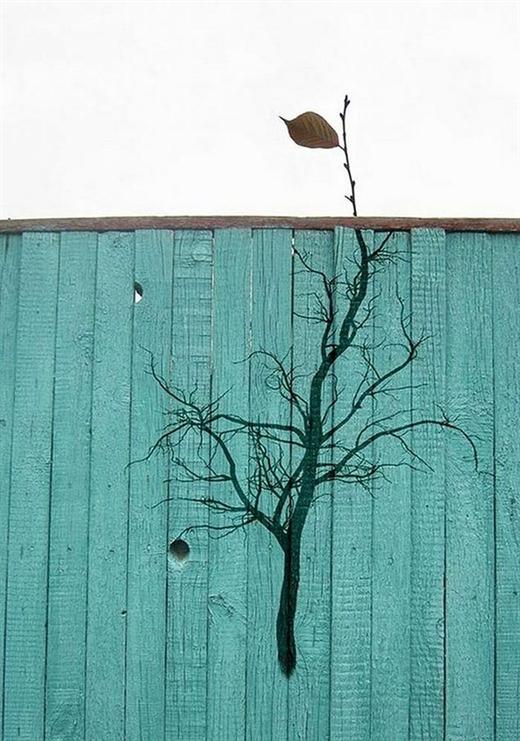 """Có cần thiết phải như vậy không? Chỉ với một cành cây bé xíu còn mỗi một """"chiếc lá cuối cùng"""" mà nghệ sĩ nhà ta phải nhọc công vẽ cả nguyên một cành cây khô bên dưới hàng rào gỗ. Đúng là đã đam mê thì bất chấp mất thời gian các chế nhỉ?"""