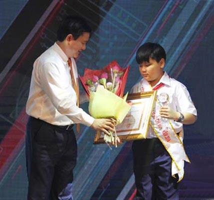 Bí thư Thành ủy TP HCM Đinh La Thăng trao bằng khen cho em Tô Huỳnh Phúc - học sinh lớp 6A Trường THPT chuyên Trần Đại Nghĩa Ảnh: HOÀNG TRIỀU
