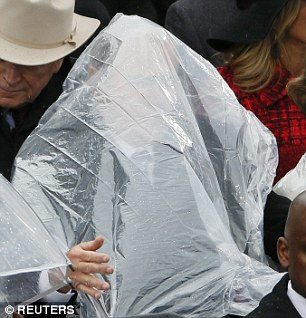 Ông Bush mặc áo mưa sai cách khiến tầm nhìn bị che. Ảnh: Reuters
