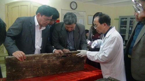 Các nhà nghiên cứu xem xét tấm ván được cho là đặt hài cốt Trạng Trình Nguyễn Bỉnh Khiêm