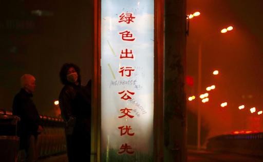 Một người đeo mặt nạ bên cạnh lời kêu gọi: Nếu bạn muốn ra ngoài, hãy sử dụng xe buýt hôm 2-1 ở Bắc Kinh. Ảnh: AP