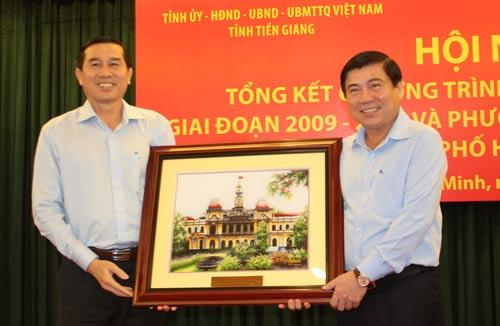 Chủ tịch UBND TP HCM Nguyễn Thành Phong (bìa phải) tặng tranh lưu niệm cho UBND tỉnh Tiền Giang