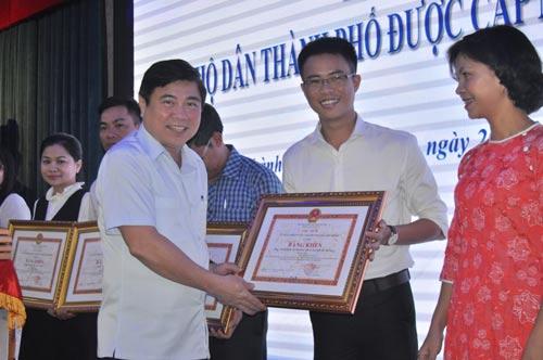 Ông Nguyễn Thành Phong, Chủ tịch UBND TP HCM, tặng bằng khen cho các cá nhân, tập thể có thành tích trong việc hoàn thành chỉ tiêu nước sạch Ảnh: TRƯỜNG HOÀNG