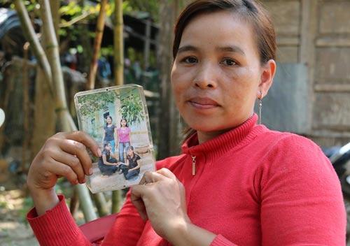 Chị A Toanh Niu cùng tấm ảnh chụp cô em gái A Toanh Nooi (ngồi, bên trái)