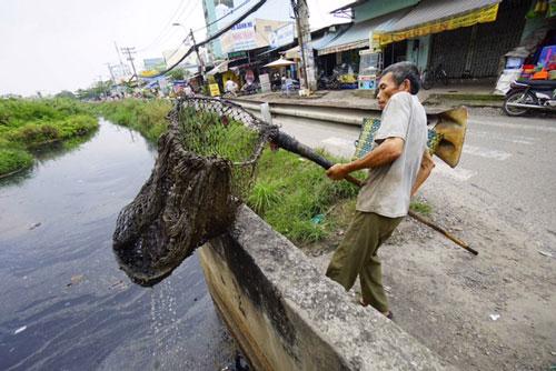 Mỗi ngày có hàng triệu người đang thầm lặng làm những việc tốt. Trong ảnh: Ông Nguyễn Ngọc Đức hằng ngày vớt rác làm sạch kênh Chiến Lược (quận Bình Tân, TP HCM) Ảnh: HOÀNG TRIỀU