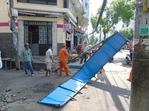Cơ quan chức năng quận Bình Thạnh tháo dỡ biển khu phố văn hóa lấn chiếm vỉa hè Ảnh: BÁCH KHOA