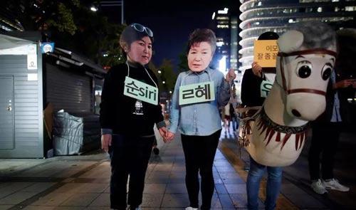 Những người biểu tình mang mặt nạ bà Choi Soon-sil (trái) và bà Park Geun-hye (phải) yêu cầu xử tội bà Choi và truất phế bà Park Ảnh: REUTERS