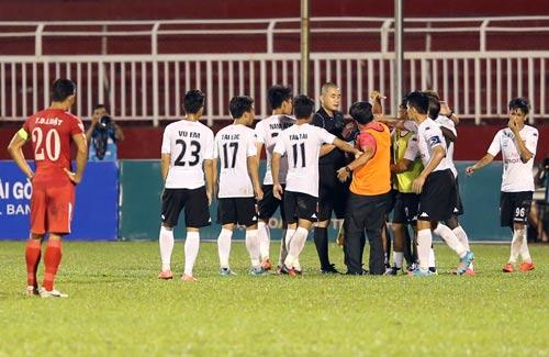 Trọng tài Nguyễn Trọng Thư bị các cầu thủ Long An phản ứng sau quyết định thổi 11 m gần cuối trận đấu với chủ nhà TP HCM tối 19-2 Ảnh: QUANG LIÊM