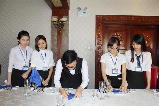 Học sinh một trường trung cấp nghề học nghiệp vụ bàn nhà hàng tại khách sạn 4 sao trong giờ thực tế
