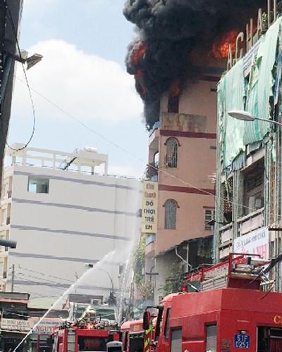 Hình ảnh ghi lại cảnh tòa nhà sát chợ Kim Biên, quận 5 cháy ở tầng 5 nhưng vòi nước chỉ phun đến tầng 3.