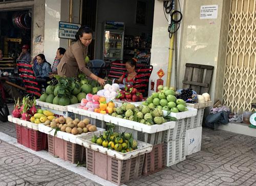 Một người dân bán trái cây trên đường Kinh Dương Vương, quận Bình Tân, TP HCM kinh doanh bên trong vạch sơn Ảnh: Lê Phong
