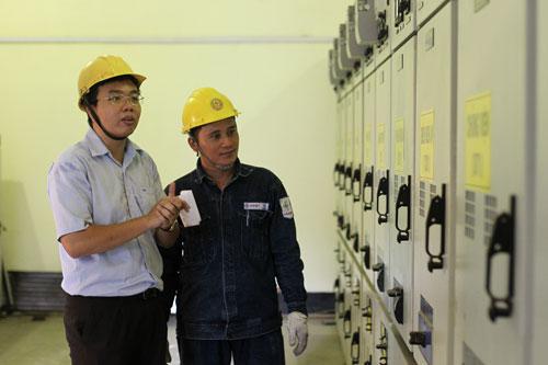 Anh Lê Duy Phúc (bìa trái) trong một trạm điện ứng dụng đề tài nghiên cứu khoa học của mình Ảnh: Hoàng Triều