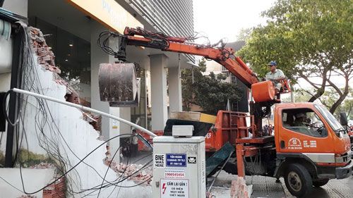 Lực lượng chức năng tháo dỡ bức tường cao 4 m trước Công ty Hoa tiêu hàng hải Khu vực 1 (đường Đinh Tiên Hoàng, phường Bến Nghé, quận 1, TP HCM) sáng 6-3 Ảnh: SỸ ĐÔNG