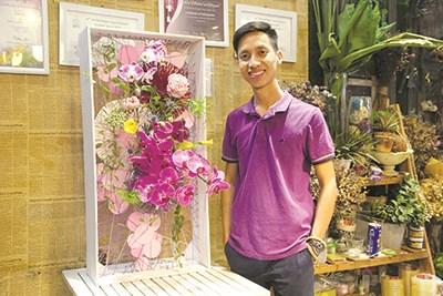 Nguyễn Phi Minh bên cạnh một tác phẩm hoa nghệ thuật vừa hoàn thành. Ảnh: H.L