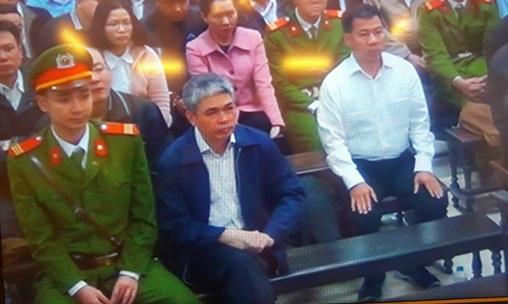 Bị cáo Nguyễn Xuân Sơn, tóc bạc, ngồi hàng đầu trong phiên toà sáng 28-2 - Ảnh chụp qua màn hình