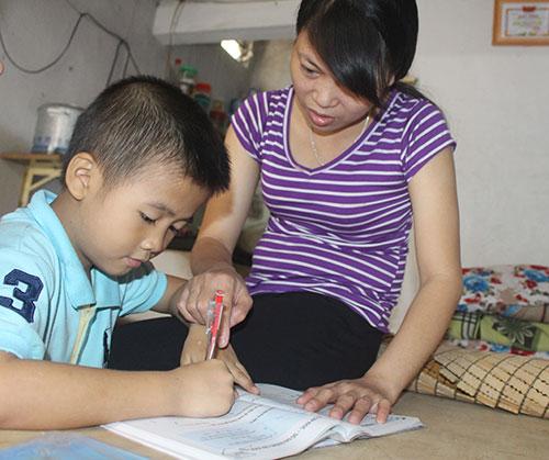 Tranh thủ ngày chủ nhật được nghỉ, chị Lê Thị Lưu kèm con trai học tập
