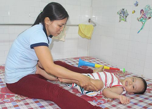 Chị Nguyễn Thị Nga tập vật lý trị liệu cho con tại phòng trọ