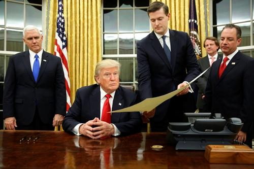 Tân Tổng thống Mỹ Donald Trump đã ký những giấy tờ đầu tiên tại phòng Bầu dục. Ảnh: Reuters