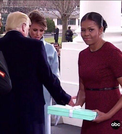 Khuôn mặt lúng túng của bà Obama khi nhận món quà mà bà Trump mang đến Nhà Trắng. Tạm thời bà không biết phải cất nó đi đâu. Ảnh: ABC