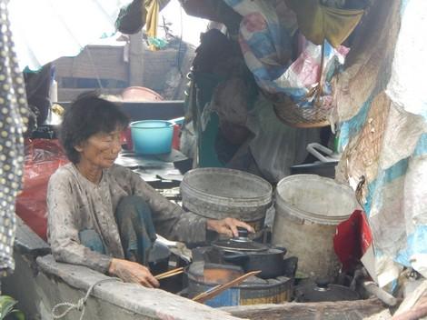Bà Hai cặm cụi nấu ăn trong chiếc thuyền mục ruỗng.