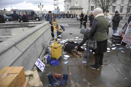 Người phụ nữ bị thương đang nằm trên cầu Westminster. Ảnh: Reuters