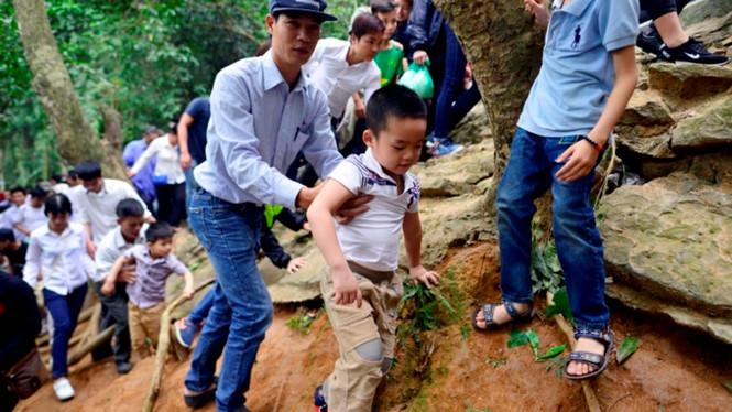 Người dân leo vách đá, bám đường rừng đi lên đền Thượng. Ảnh Minh Chiến