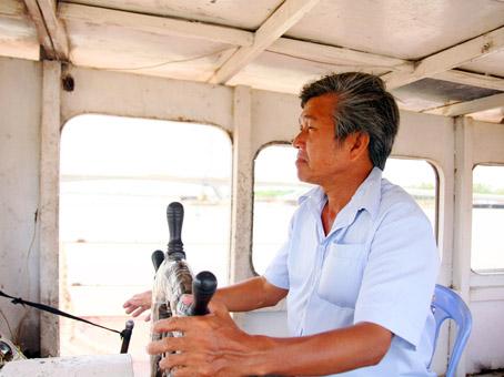 Ông Lê Văn Sung quan sát tàu thuyền qua lại trên sông ở vị trí lái phà.