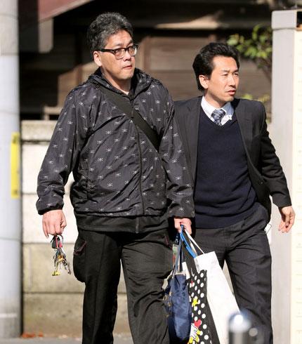 Nghi phạm bị cảnh sát đưa đi khoảng 8 giờ sáng 14-4-Ảnh: Asahi