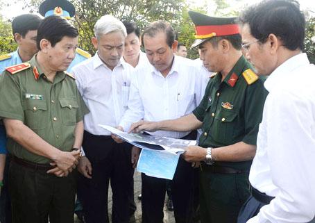 Phó thủ tướng thường trực Chính phủ Trương Hòa Bình và Bí thư Tỉnh ủy Nguyễn Phú Cường (giữa) nghe lực lượng tìm kiếm giới thiệu về các tài liệu có liên quan đến hố chôn liệt sĩ tại Sân bay Biên Hòa ngày 18-3-2017.
