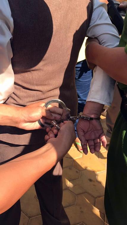Bà Dung bị các bảo vệ khống chế, còng tay khi bà dọa dùng xăng tự thiêu, hôm 23-3.