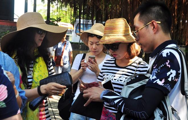 Phiên dịch Trung Quốc đổi nhân dân tệ cho du khách ở phố biển Nha Trang. Ảnh: Minh Hoàng.