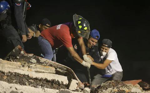 Lực lượng cứu hộ đào bới đống đổ nát của một tòa nhà. Ảnh: AP