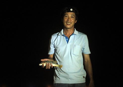 Chiến lợi phẩm của ông Vân sau một đêm đi câu chỉ là con cá nhỏ nhưng ông vẫn vui vẻ. Ảnh: Nguyễn Đông