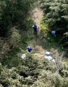 Cảnh sát tìm kiếm quanh nơi phát hiện balô của bé gái. Ảnh: ASAHI