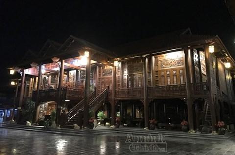 Ngôi nhà sàn lung linh khi đêm về. Với tổng diện tích là 500m2, nhà sàn 2 tầng nằm trong khuôn viên riêng biệt rộng 2000m2 và được làm từ 500m3 gỗ lim lõi. Theo lối kiến trúc của người dân tộc Thái, nhà sàn gồm 7 gian khách, 3 gian mái, mỗi gian rộng 3,8m.