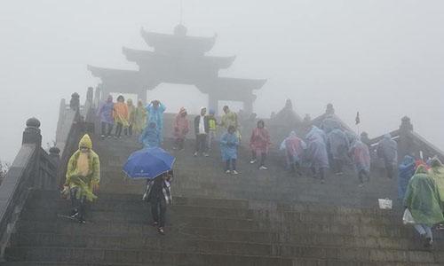 Trời mù sương, đường trơn trượt do mưa khiến các du khách phải cẩn trọng đi từng bước;Ảnh: Phương Vũ
