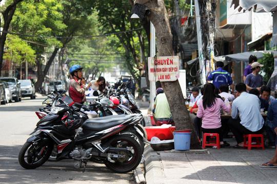 Trên đường Lê Thị Hồng Gấm, một quán ăn chiếm dụng vỉa hè làm nơi đặt bàn ghế, lòng đường cũng ngang nhiên được làm nơi giữ xe cho khách.