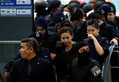 Nghi phạm Siti Aisyah mặc áo chống đạn bị bao vây bởi cảnh sát. Ảnh: Reuters