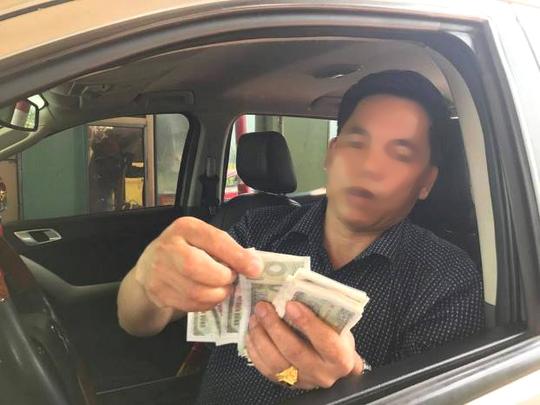 Một người dân thị xã Kỳ Anh đang dùng tiền lẻ trả phí ở Trạm thu phí BOT Cầu Rác